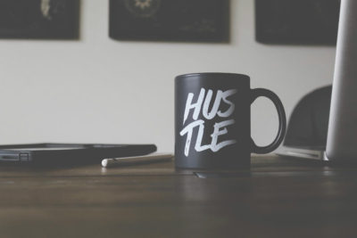 mug on a desk that says hustle
