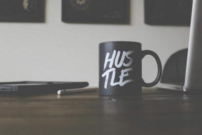 mug on a desk that says hustle