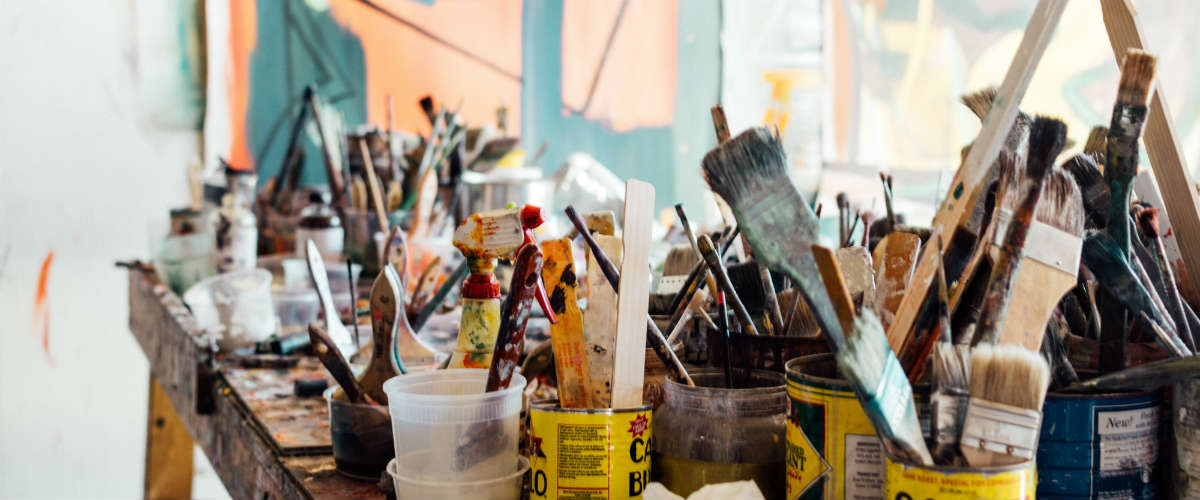 messy table full of paint brushes