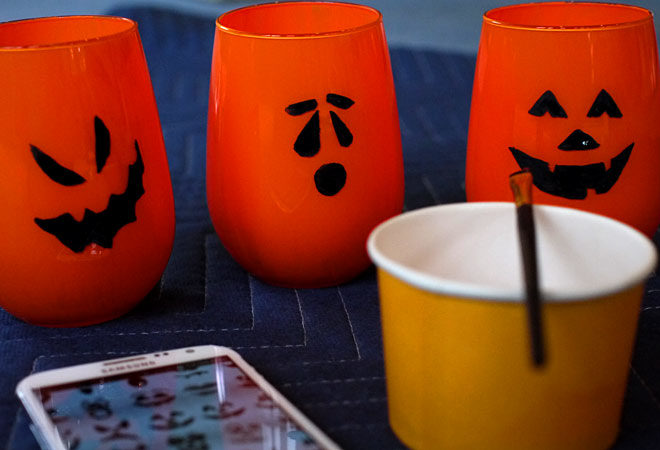 finished painting faces on the Jack-O-Lantern candle holders