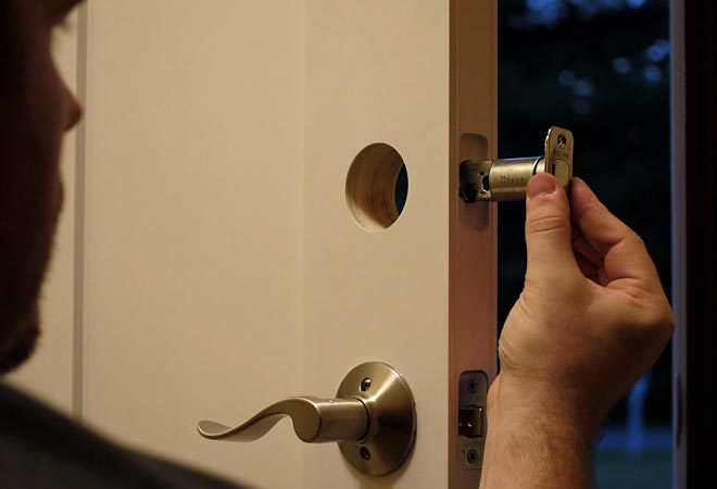 inserting the deadbolt bolt into the door